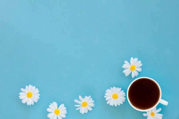Top view tea cup surrounded by flowers with copy space Free Photo