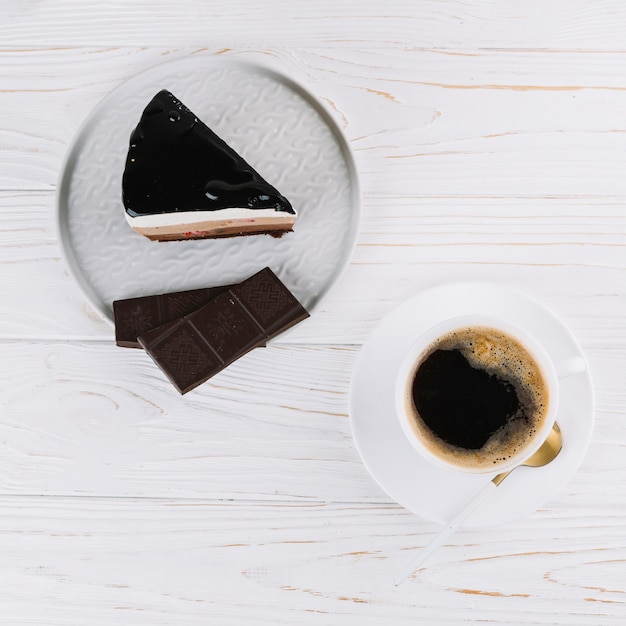 Top view of tea; delicious pastry with chocolate bar for breakfast on table Free Photo