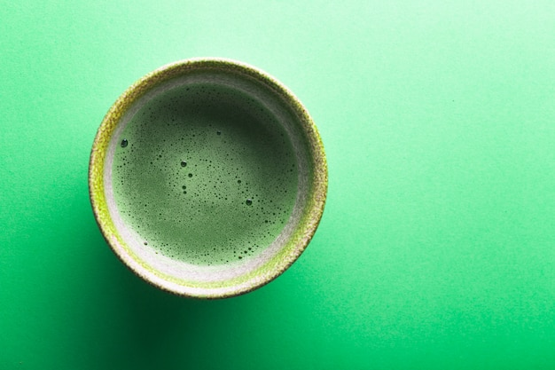 Top view of tea matcha in a bowl on greeen surface Premium Photo
