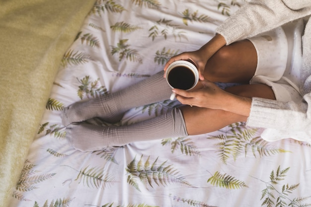 Top view of a teenage girl sitting on bed holding coffee cup Free Photo