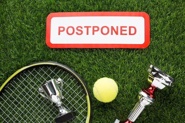 Top view tennis elements arrangement with postponed sign Free Photo