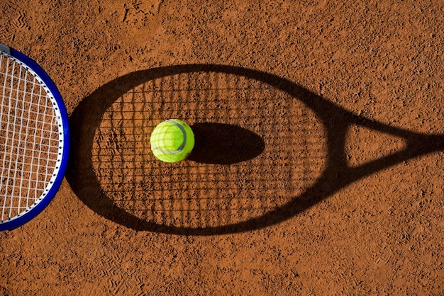 Top view tennis racket shadow with a ball Free Photo