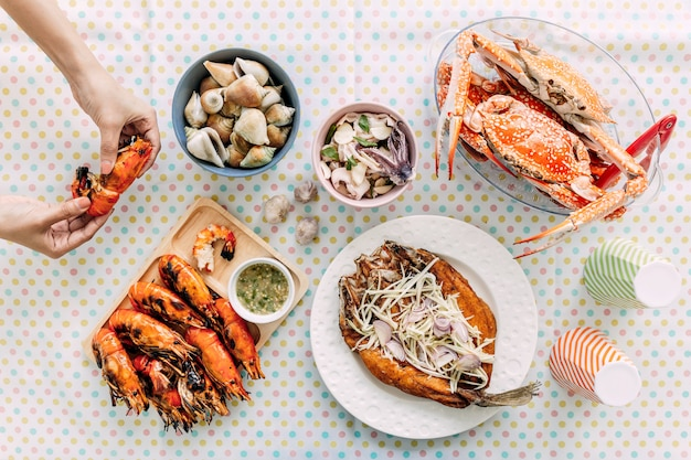 Top view of thai seafoods are grilled prawns (shrimps) in the shell, steamed crabs, grilled laevistrombus canarium, grilled squid and deep fried sea bass with sweet fish sauce and mango salad. Premium Photo