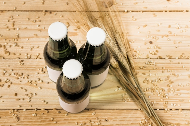 Top view of three closed beer bottles and ears of wheat on wooden background Free Photo