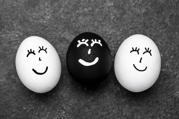 Vista dall'alto di tre diverse uova colorate con facce per il movimento della materia delle vite nere Foto Gratuite