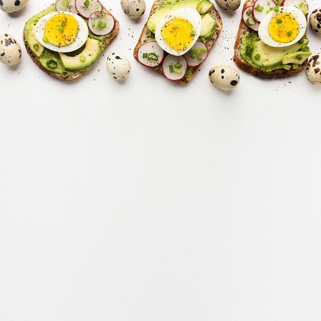 Vista dall'alto di tre panini con uova e avocado con spazio di copia Foto Gratuite
