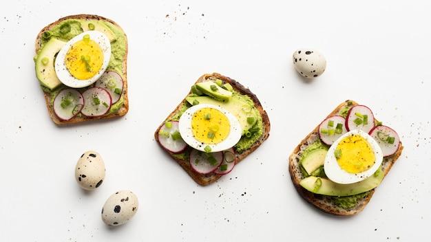 Vista dall'alto di tre panini con uova e avocado Foto Gratuite