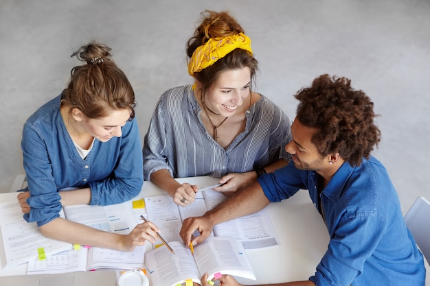 Top view of three students sitting at table surrounded with books and copybooks, discussing something with great interest, having happy expression. brainstroming, team work and education concept Free Photo