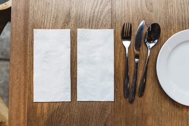 Top view of tissue napkins and cutlery over wooden table. for food banner. Premium Photo