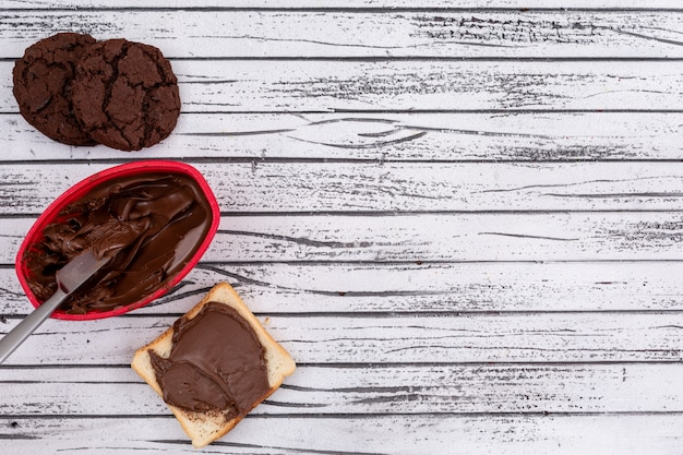 Top view of toast with chocolate and cookies and copy space on white wooden background horizontal Free Photo