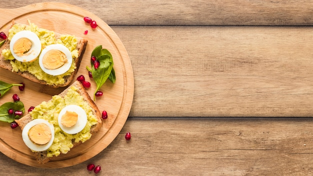 Top view of toasted bread with boiled egg on cutting board Free Photo