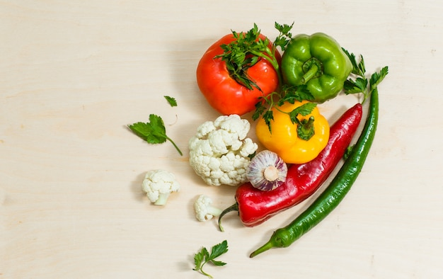Top view tomato with peppers, cauliflower, greens, chili peppers on white. horizontal Free Photo