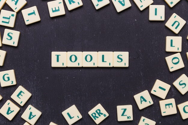 Top view of tools text on scrabble letters over black backdrop Free Photo