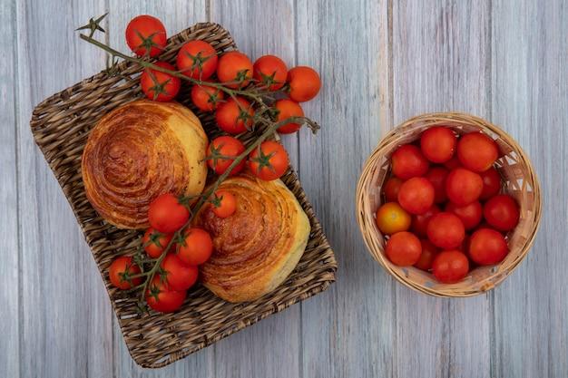 Vista dall'alto della tradizionale pasticceria azerbaigiana gogal su un vassoio di vimini con pomodori su un secchio su un grigio sfondo di legno Foto Gratuite