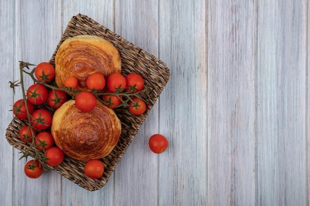 Vista dall'alto della tradizionale pasticceria azerbaigiana gogal su un vassoio di vimini con pomodori a grappolo su un grigio sfondo di legno con spazio di copia Foto Gratuite