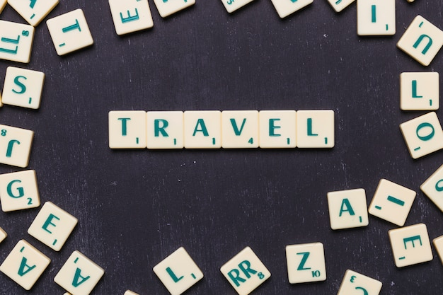 Top view of travel text with scrabble letters over black backdrop Free Photo
