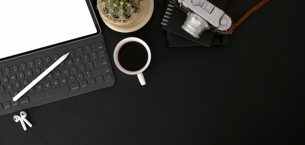 Top view of trendy photographer workplace with mock up digital tablet ,camera and office supplies on black table Premium Photo