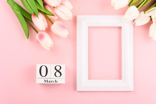 3月8日のカレンダーと上面図チューリップの花とフォトフレーム。幸せな女性の日のコンセプト Premium写真