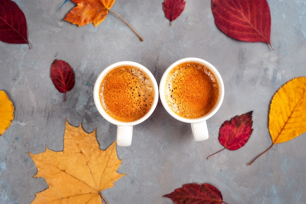 Top view of two cups of coffe around yellow leaves Premium Photo