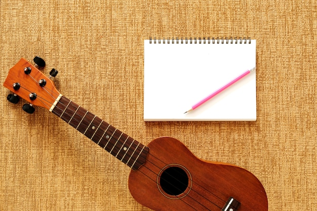 Top view of ukulele with notebook and pencil Premium Photo