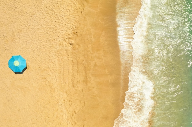 Top view of umbrella on golden sandy beach washed by mediterranean sea waves Free Photo