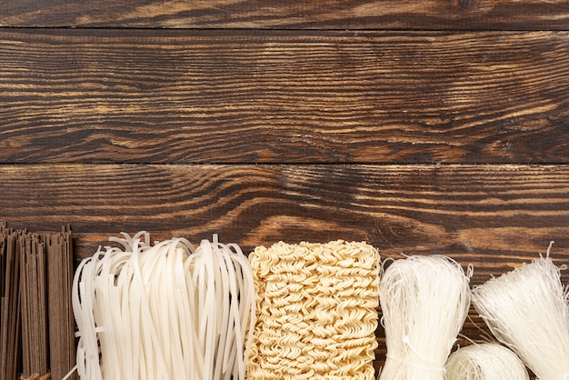 Top view uncooked assortment of noodles on wooden background with copy space Premium Photo