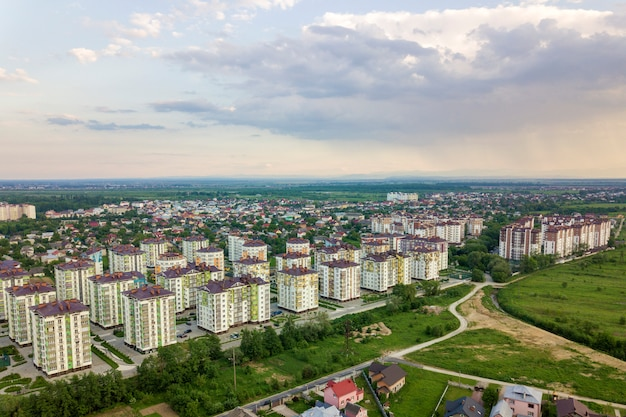 Top view of urban developing city landscape with tall apartment buildings and suburb houses. drone aerial photography. Premium Photo