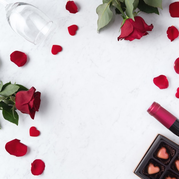 Top view of valentine day chocolate with rose and wine, festive gift design concept for special holiday dating. Premium Photo