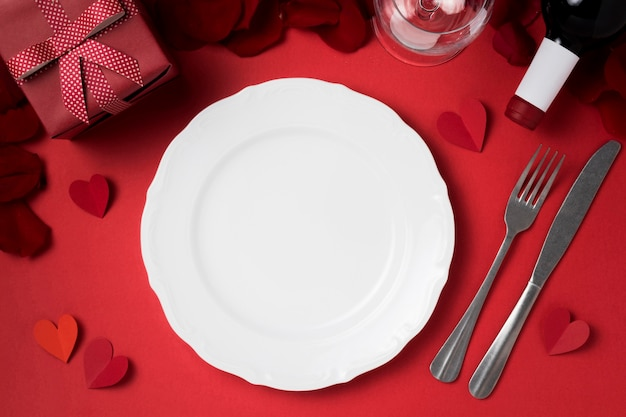 Top view of valentine's day table set with plate and gift Free Photo