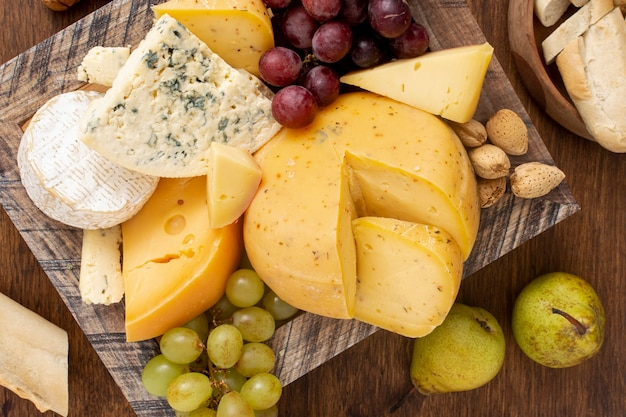 Top view variety of cheese with fruits Free Photo