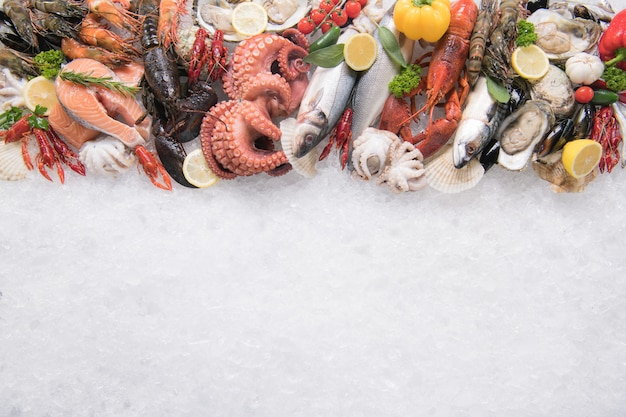 Top view of variety of fresh fish and seafood on ice with copy-apace Premium Photo