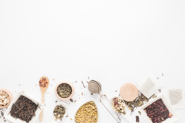 Top view of variety of herbs; spoon; tea strainer; dry tea leaves arranged on white background Free Photo