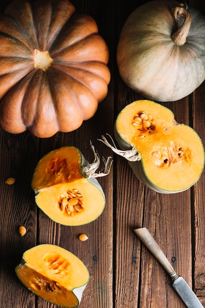 Top view variety of pumpkins on wooden background and knife Free Photo