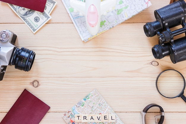 Top view of various traveler accessories on wooden backdrop Free Photo