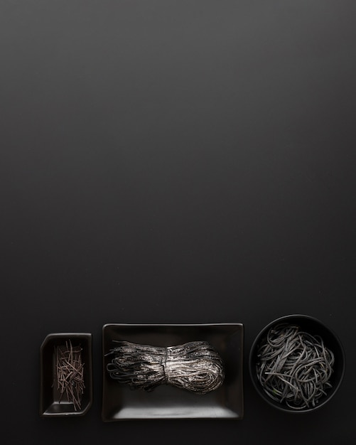 Top view various types of squid ink pasta in bowls Free Photo