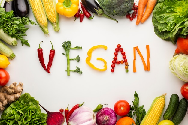 Top view vegan lettering made out of vegetables on white background Premium Photo