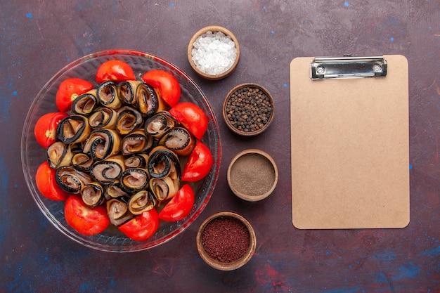 暗い背景にナスと調味料をスライスして巻いたトマトの上面図野菜ミール 無料写真