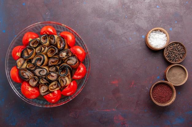 Вид сверху овощной муки, нарезанных и свернутых помидорами с баклажанами и приправами на темно-фиолетовом фоне Бесплатные Фотографии