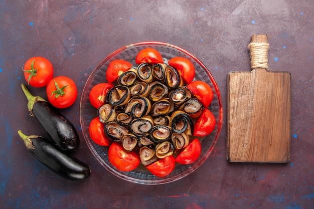 暗い背景にナスとスライスして巻いたトマトの上面図野菜ミール 無料写真