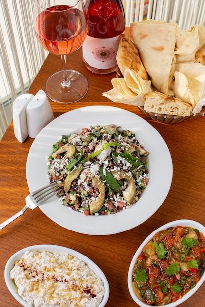 Un pasto di verdure con vista dall'alto con pane di carne e vino sul tavolo durante la cena del pasto diurno Foto Gratuite