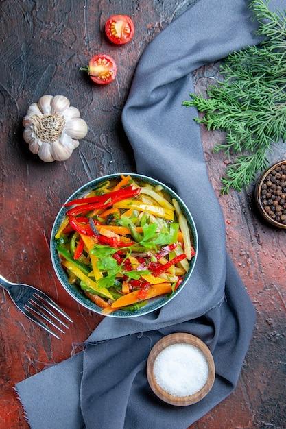 Vista dall'alto di insalata di verdure nella ciotola pepe nero ramo di abete blu oltremare scialle aglio sale sul tavolo rosso scuro Foto Gratuite
