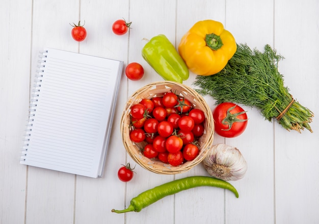 Top view of vegetables as tomato pepper garlic dill with note pad on wooden surface Free Photo