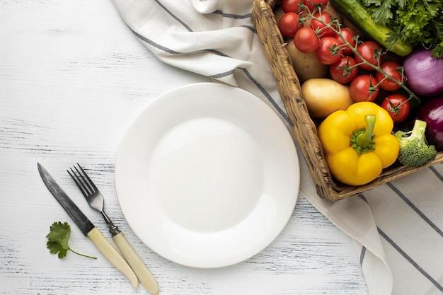 Корзина с овощами и тарелка, вид сверху Premium Фотографии