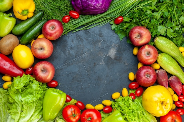 Top view vegetables and fruits lettuce tomatoes cucumber dill cherry tomatoes zucchini green onion parsley apple lemon kiwi free space in center Free Photo