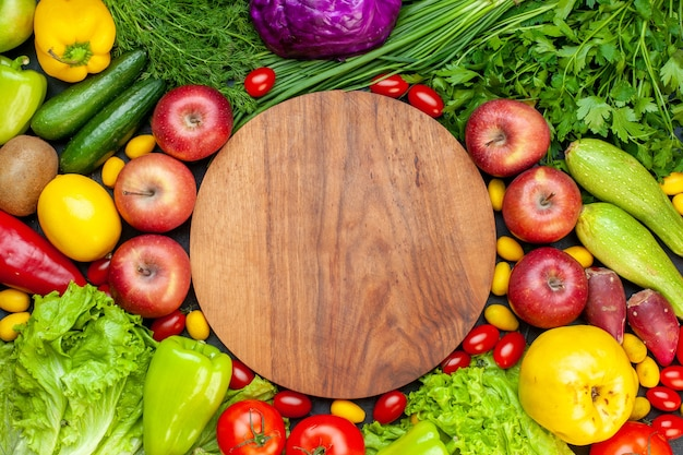 Top view vegetables and fruits lettuce tomatoes cucumber dill cherry tomatoes zucchini green onion parsley apple lemon kiwi round wood board in center Free Photo