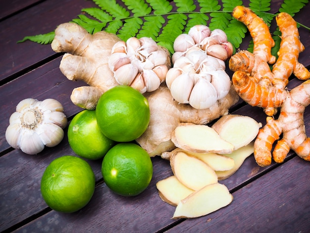 Premium Photo | Top view of vegetables and herbs for cooking with turmeric root, ginger, garlic and lemon fruit on fern leaves on wooden table in kitchen.