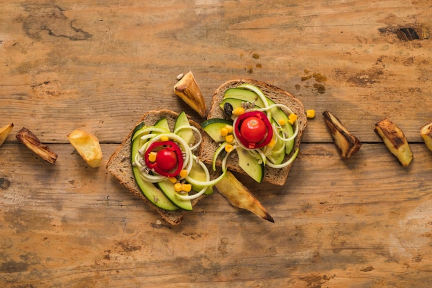 Top view of vegetables sandwich with roasted potato slice on wooden table Free Photo