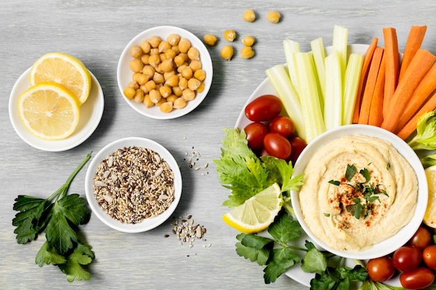 Top view of vegetables with hummus and lemons Free Photo