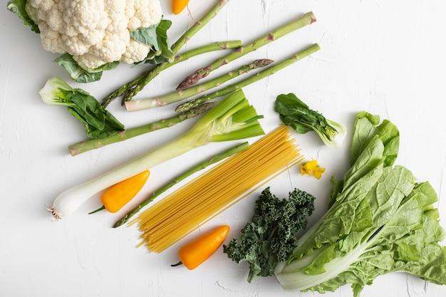 Вид сверху на овощи и сырые спагетти Premium Фотографии