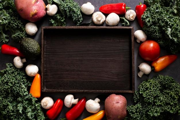 Le verdure con vista dall'alto si mescolano con un vassoio di legno vuoto Foto Gratuite